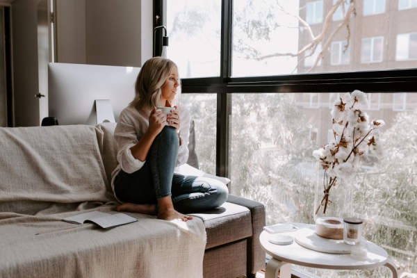 woman sitting on couch drinking tea