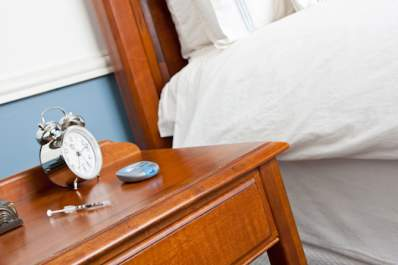 Syringe and glucose meter with alarm clock on nightstand.