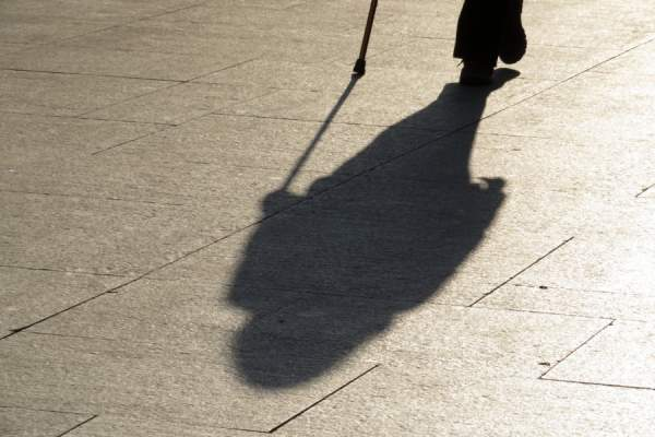 person walking with cane, casting long shadow