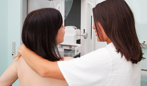 Young woman has mammogram with nurse helping