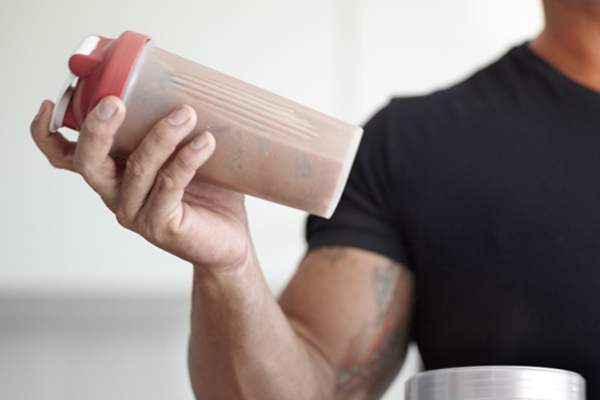 Strong man holding protein shake image.