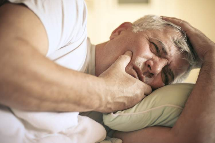 Senior man lying in bed having dental pain.