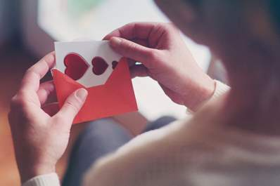 Woman putting a valentine card with hearts in a red envelope.