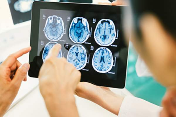 Doctor and patient using digital tablet to look at brain scans.