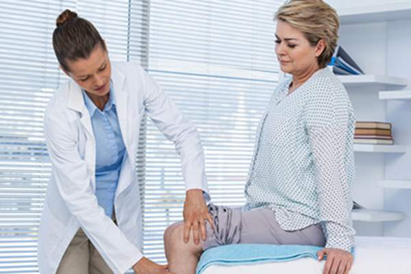 Doctor examining a woman's knee.