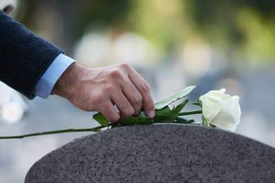 man laying a white rose on grave image
