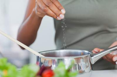 Woman adding salt to pot cooking on stove.