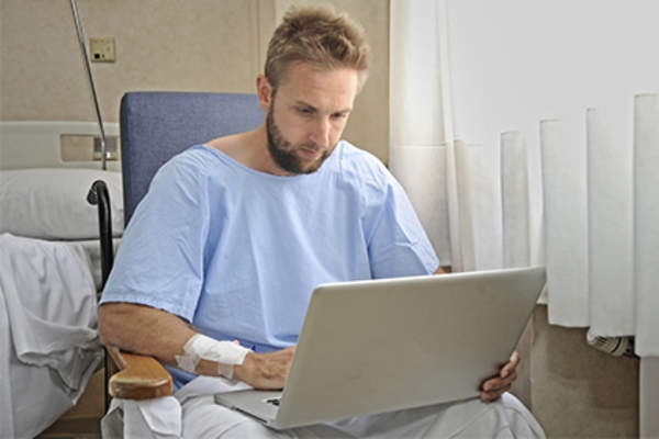 Male patient looking for online health information in hospital on laptop.