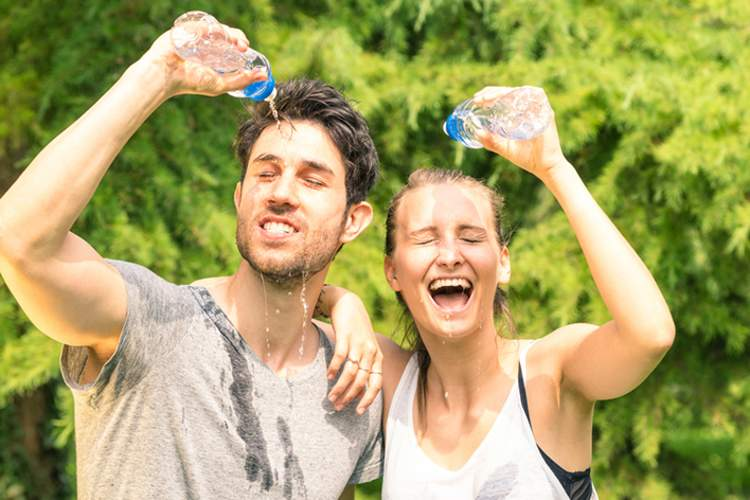Tired, sweaty couple pouring water on their heads after exercise.