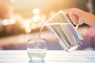 Pitcher of water pouring into glass, staying hydrated is important with hep c.