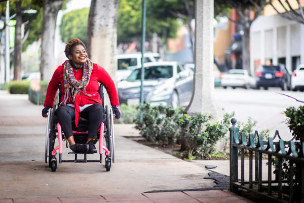 woman smiling in wheelchair going down the street