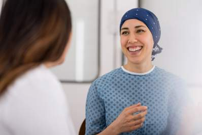 Smiling cancer patient talking to her doctor.