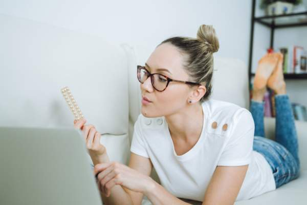 woman on couch looking at birth control pills