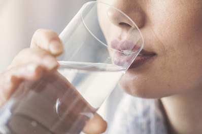 Woman drinking from a glass of water.