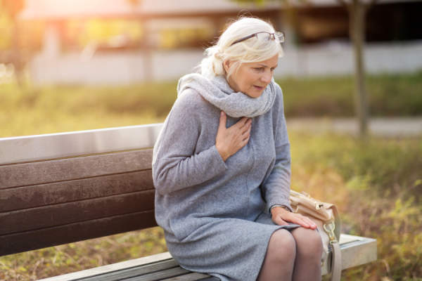 senior woman clutching heart sitting outside