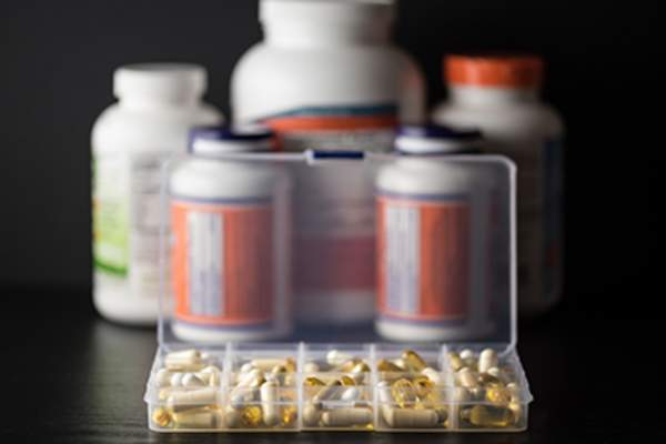 Supplements in daily pill box in front of bottles