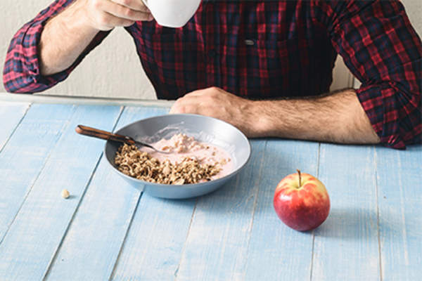 Man eating a healthy breakfast of cereal, coffee, and an apple.