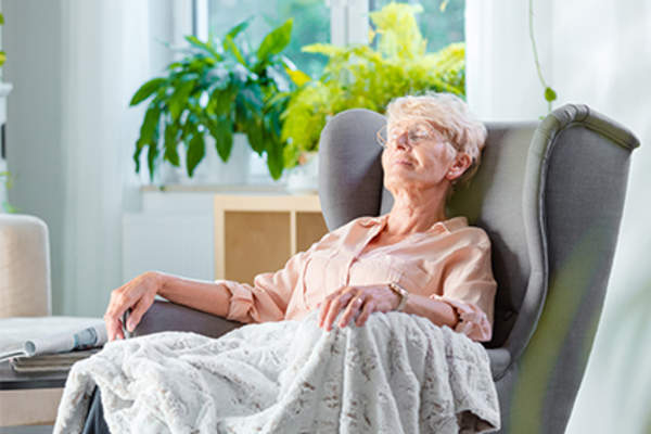 Senior woman sleeping a chair.