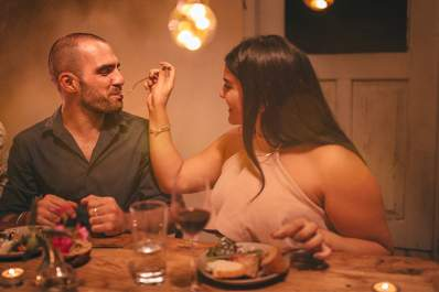 Young woman feeding her partner at romantic dinner.