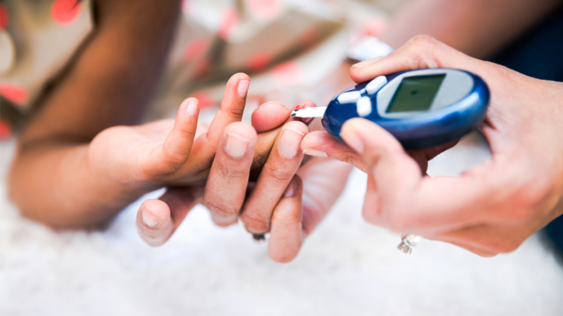 Child having blood sugar test.