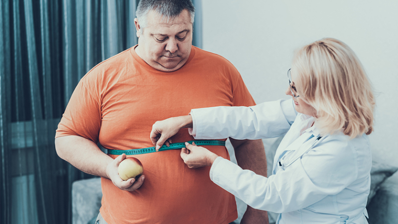 Doctor measuring obese man's waist size.