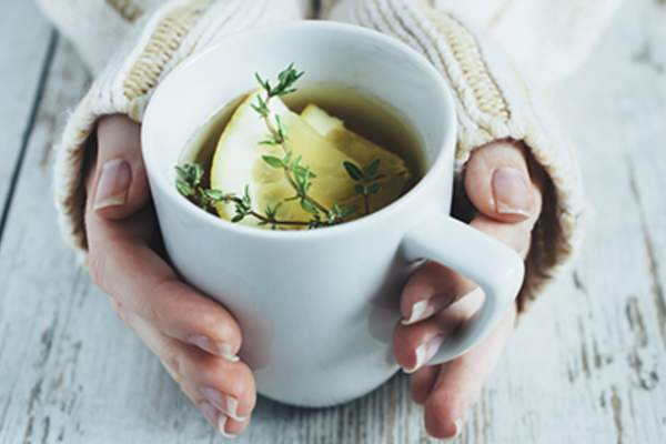 Cup of tea with thyme herb and lemon slices.