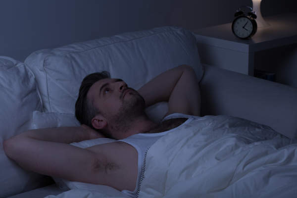 Man in bed wide awake in a dark room