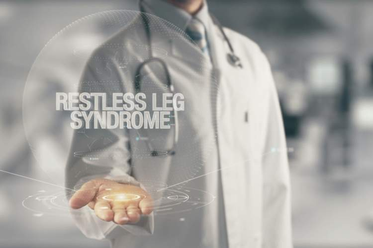 """Restless leg syndrome"" holographic text in doctors hands."