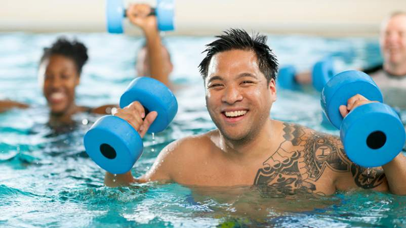 Smiling man in water aerobics class.
