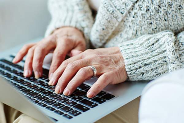 Close up of senior woman typing on laptop at home.