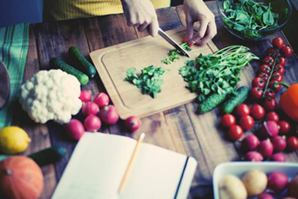 Woman preparing a meal with healthy vegetables.