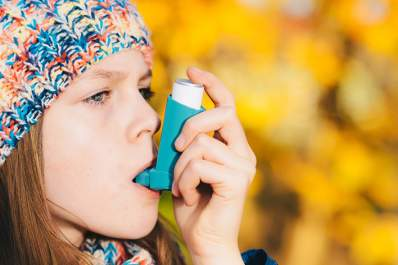 Girl using asthma inhaler in park in autumn.