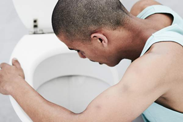 Man vomiting into a toilet.