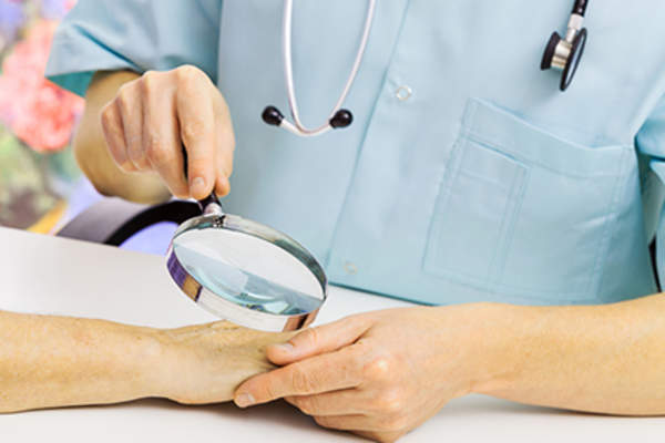 Dermatologist using magnifying glass to examine woman's skin.