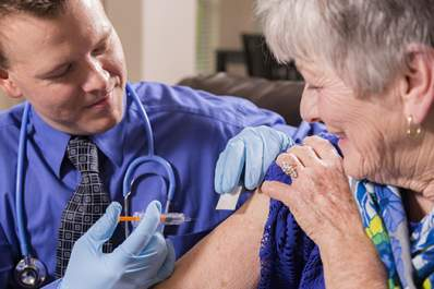 Doctor giving senior woman a vaccine.