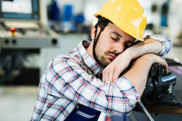 Tired worker falling asleep on job.