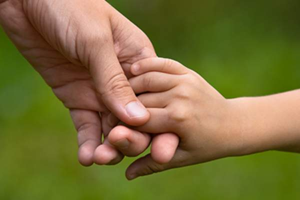 Adult holding a child's hand.