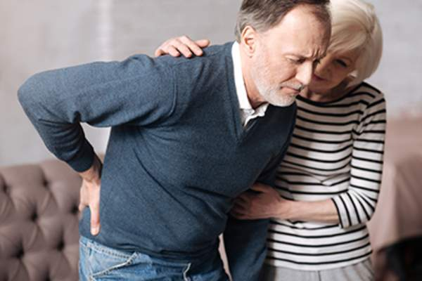 Senior man with back pain getting help from his wife.