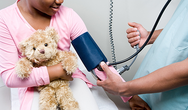 Doctor checking blood pressure of young girl holding teddy bear.