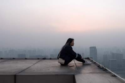 pensive woman sitting on roof