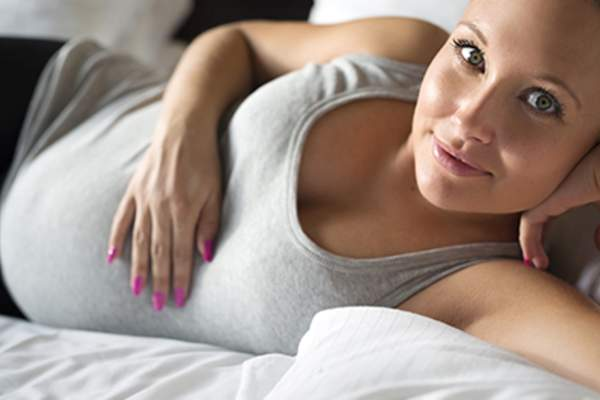 Smiling young pregnant woman lying on side in bed.