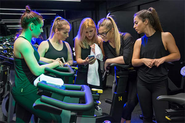 Young women comparing fitness app results after exercise class.