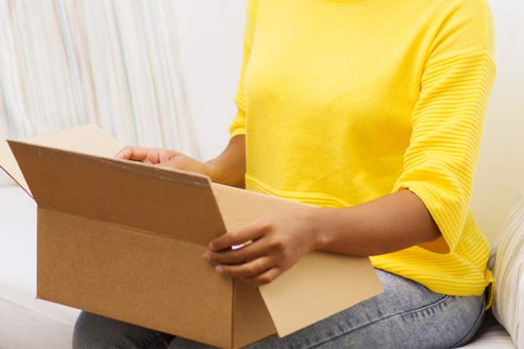 Woman opening a package at home.