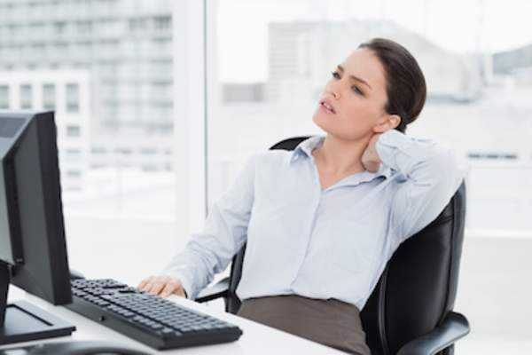 Young woman at desk with neck pain