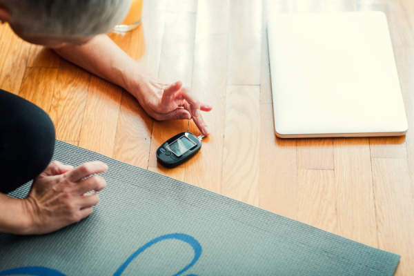 Mature Woman Doing Blood Sugar Test on yoga mat