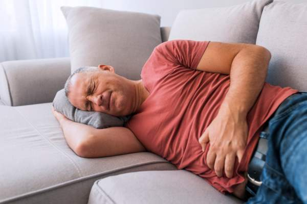 Man clutching stomach in pain