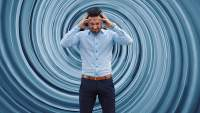 Man holding his head against spinning background, vertigo concept.