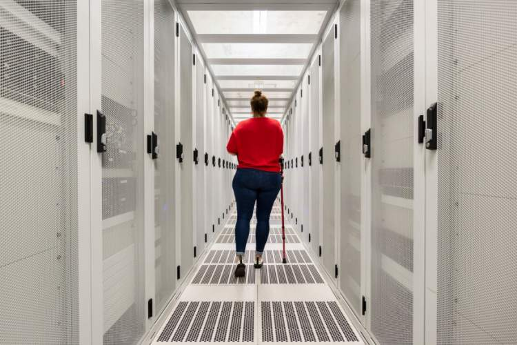 Young woman with cane walking through data center