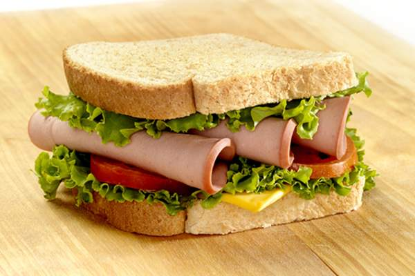 Bologna sandwich with cheese and lettuce image.