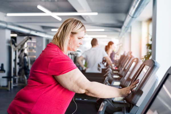 overweight woman walking on treadmill